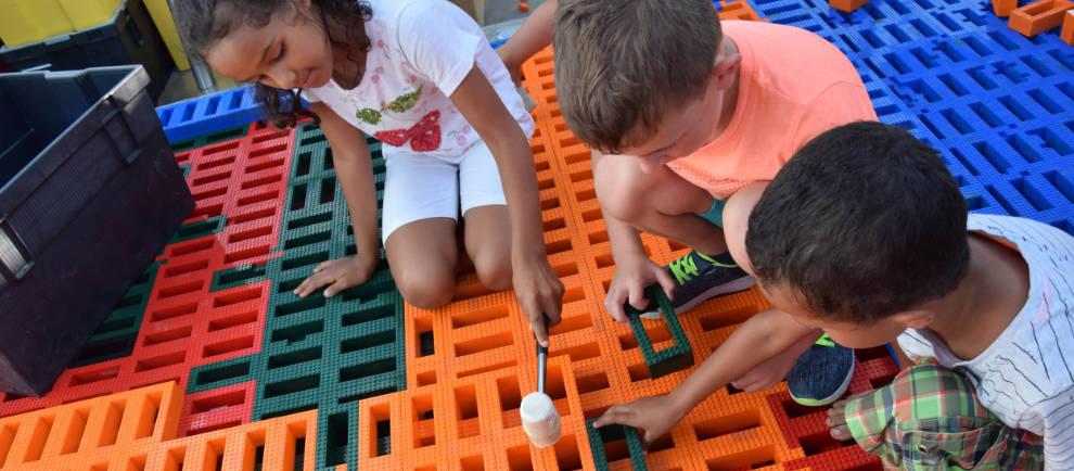Kinder bauen gemeinsam mit Legosteinen und Hammer eine riesige Lego Pyramide