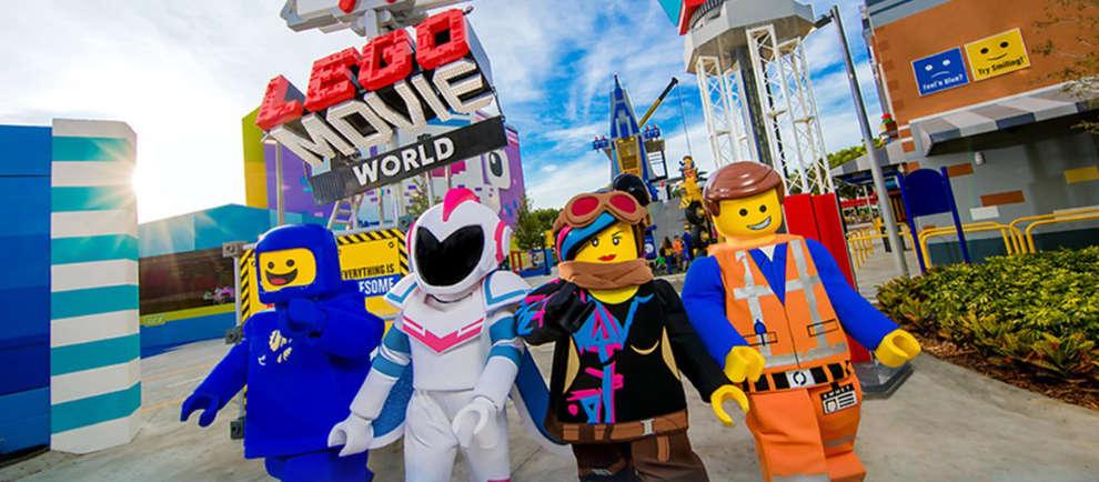 Die Helden aus dem Lego Film schreiten durch das Eingangstor der Lego Movie World