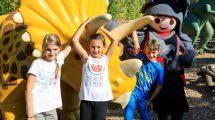 Eine Gruppe von lachenden Kindern steht vor einem gelben Dinosaurier. Mit dabei ist eine lebensgroße Playmobilfigur im Ritterkostum.