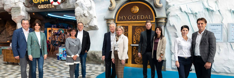 """Die Europa-Park Inhaberfamilie Mack freut sich über die Fertigstellung der neuen Wohlfühloasen – hier vor dem imposanten Eingangstor von """"Hyggedal"""". © Europa-Park Resort"""